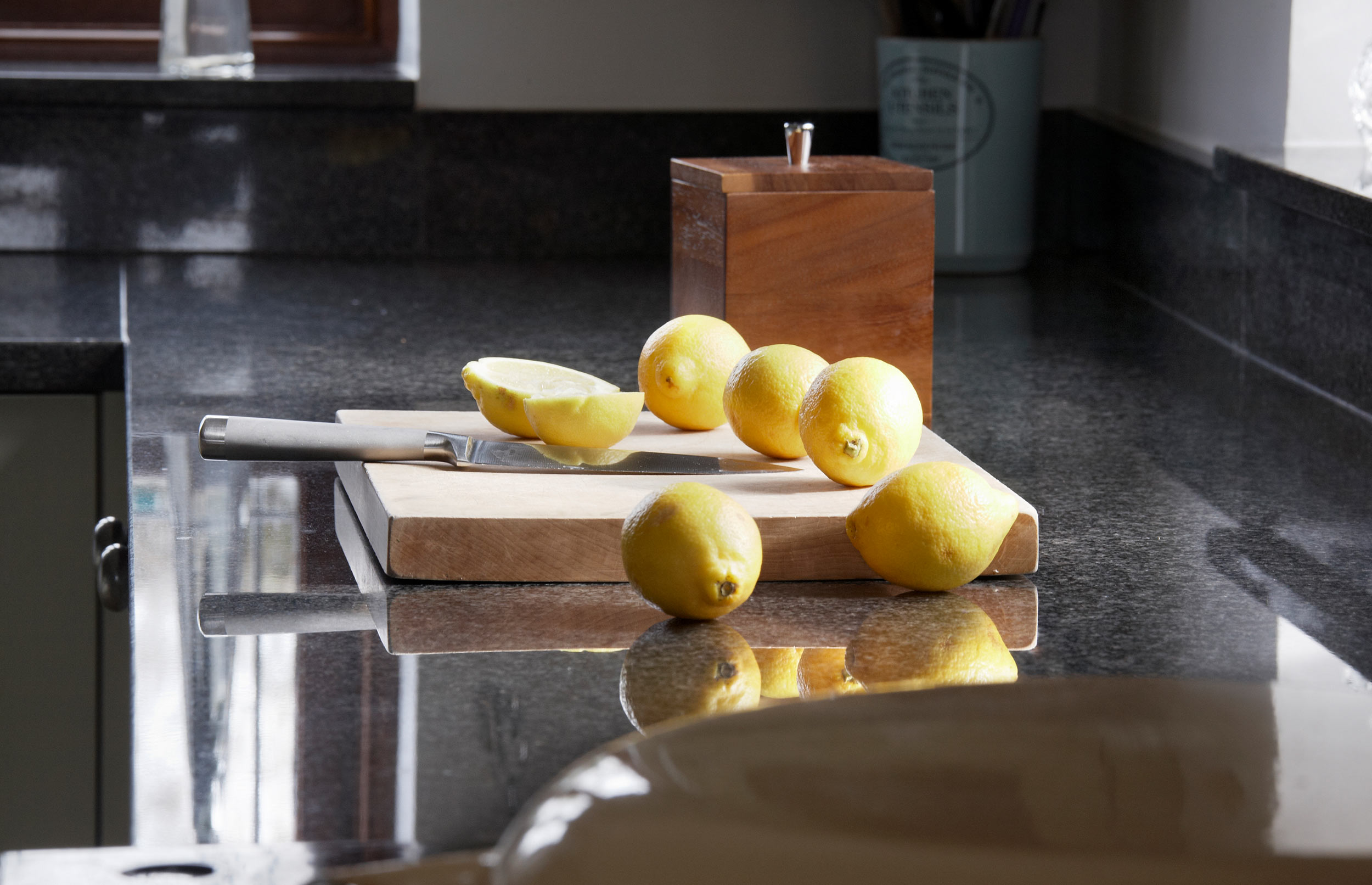 Cosy Bespoke Kitchen - Lemons on Wooden Board on Dark Top Surface